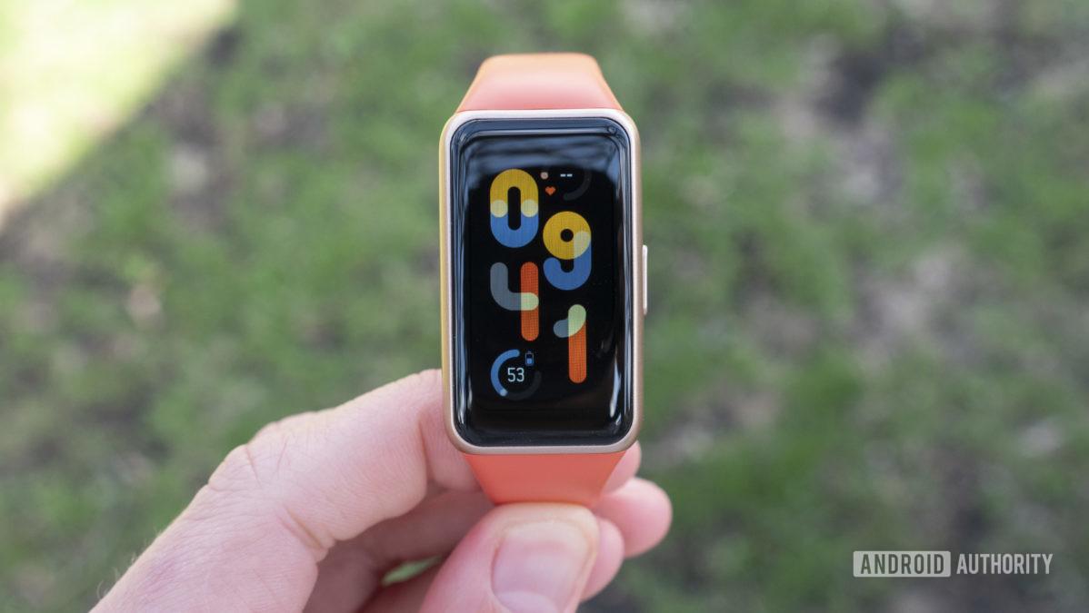 Huawei Band 6 revisa o mostrador do relógio em mãos